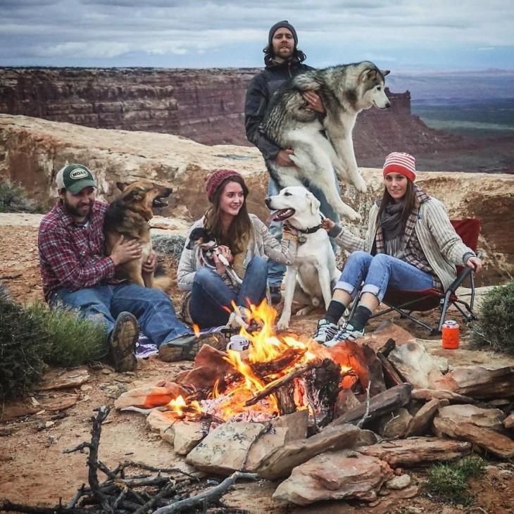 Grupo de personas con sus perros frente a una fogata en un paisaje con montañas y un poco frío