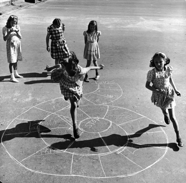 niñas jugando en una calle sobre un avioncito en el suelo
