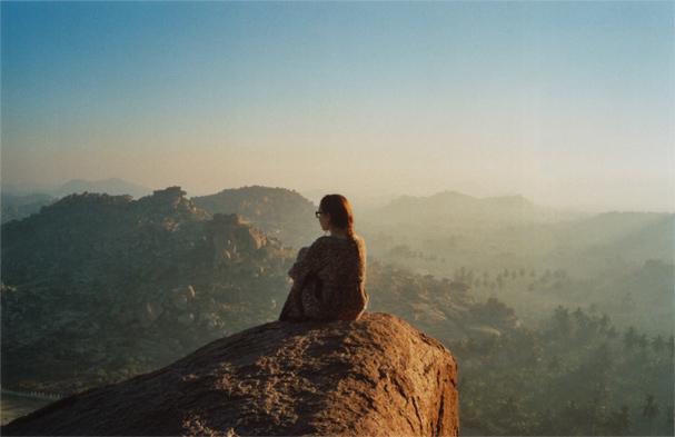 Fotografía de una chica sentada en lo alto de una montaña viendo la puesta de sol