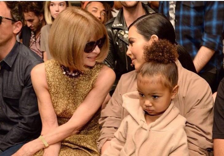 Kim Kardashian con una niña sentada en sus piernas platicando con otra mujer