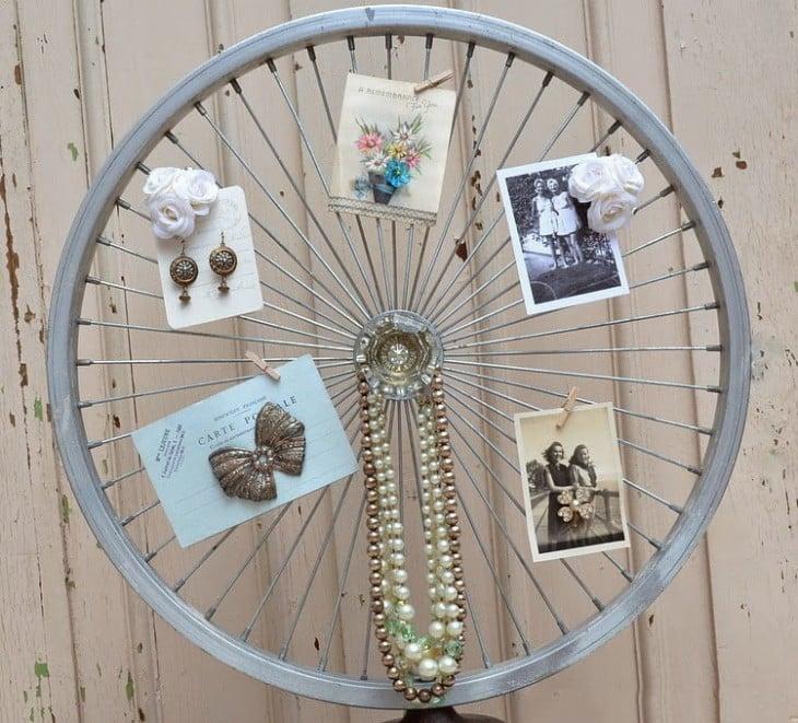 Rueda de bicicleta que sostiene joyas y algunas fotografías