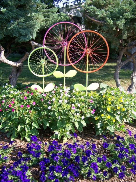 Jardín decorado con ruedas de bicicleta pintadas que simulan ser unas flores