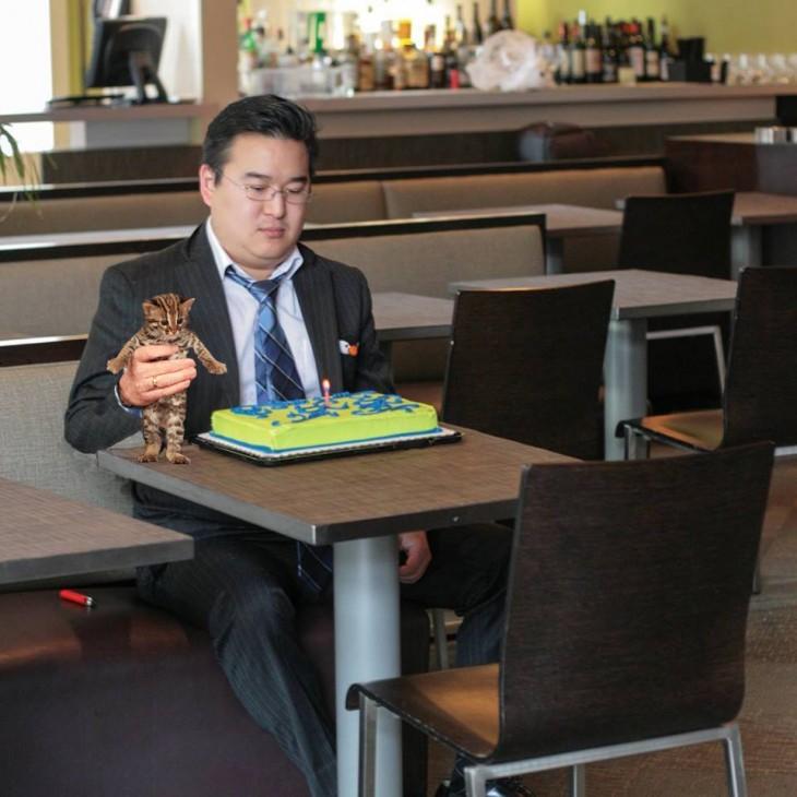 Chico frente a un pastel con un pequeño gato en su mano derecha
