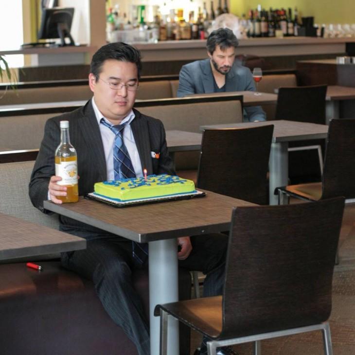 Fotografía de un chico sentado frente a la mesa de un bar con un pastel de cumpleaños y una botella en su mano con una persona detrás de él