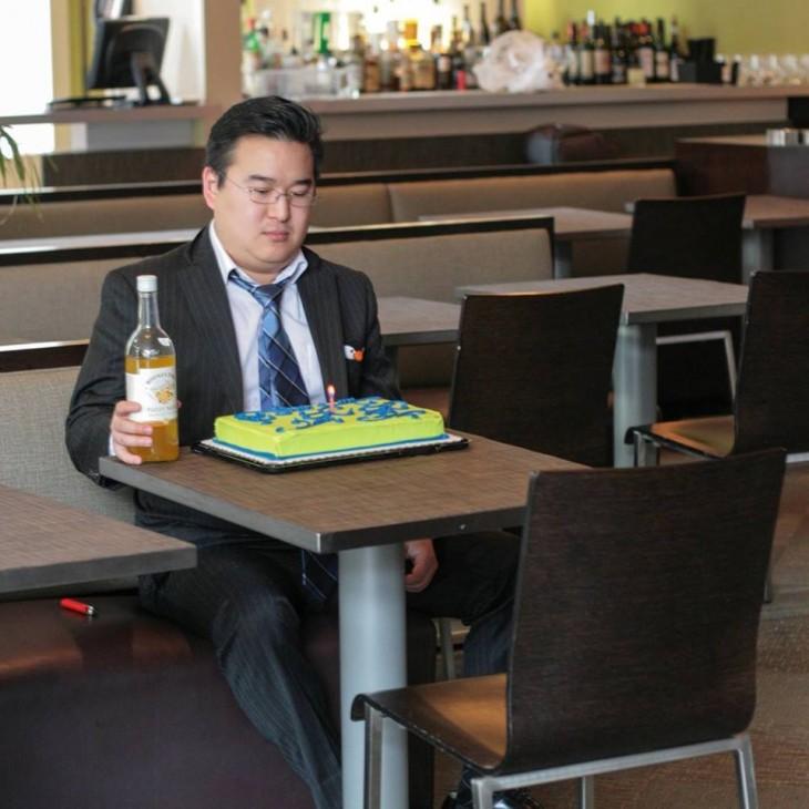 Fotografía de un chico sentado frente a la mesa de un bar con un pastel de cumpleaños y una botella en su mano