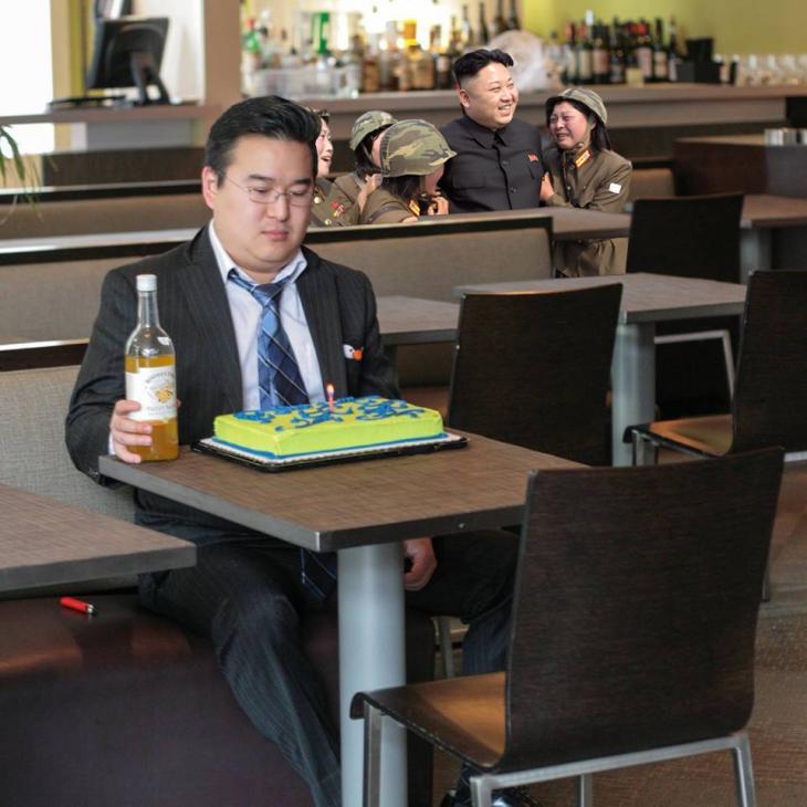 Persona con un pastel solo en la mesa y unas personas abrazándose detrás de él