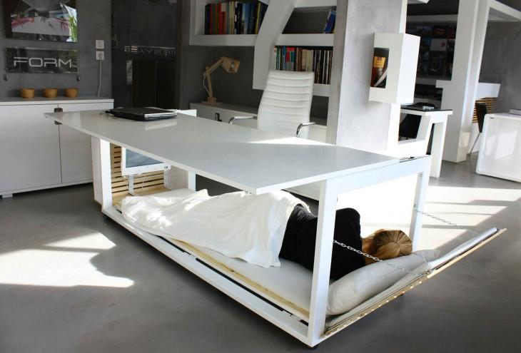 Una mujer acostada en la parte inferior de un escritorio dentro de una oficina