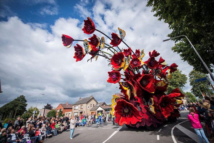 Carro en medio de un desfile con figuras de flores hechas con Dahlias