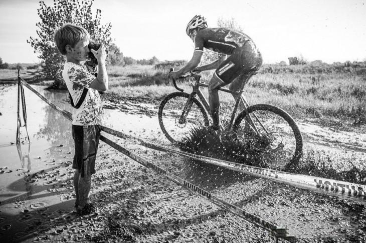 niño tomando una fotografía mientras un ciclista lo salpica de lodo
