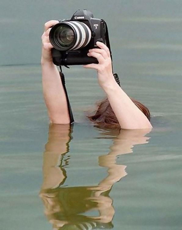 Manos de una persona sumergida en el agua tomando una fotografía