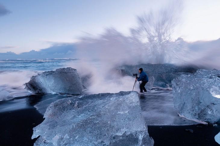Fotógrafo en medio de hielo a punto de ser arrojado por agua
