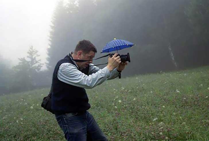 Hombre tomando una fotografía con un pequeño paraguas sobre su cámara