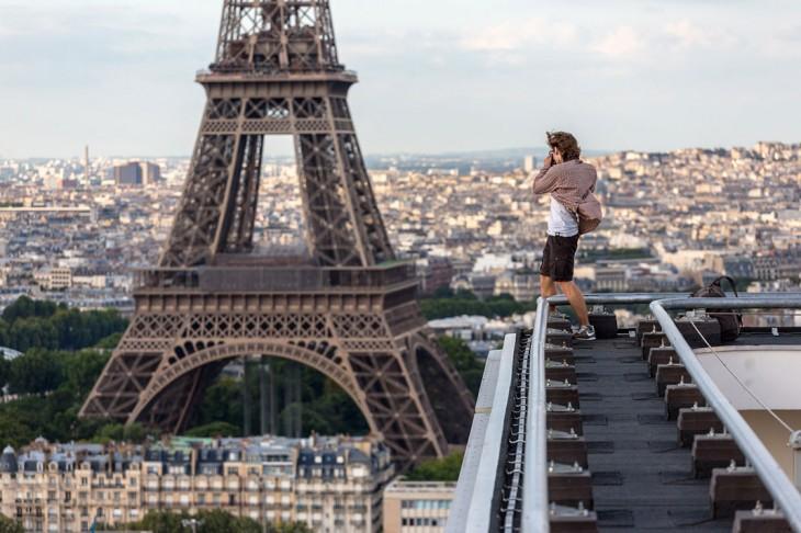 chico sobre un edificio sacando una fotografía de la torre Eifel
