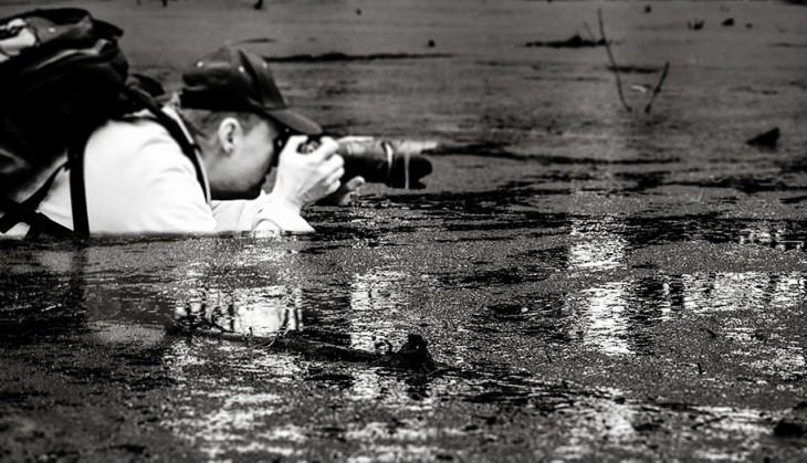 Hombre tomando una fotografía dentro de un lago a blanco y negro