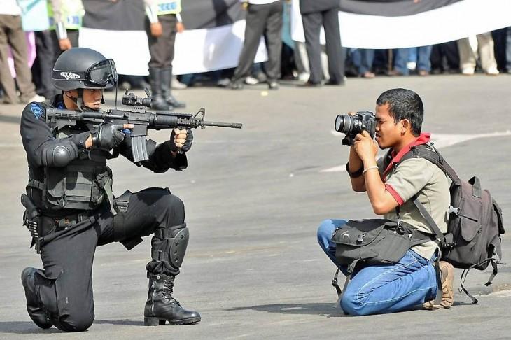 chico tomando una fotografía frente aun hombre señalándolo con un arma