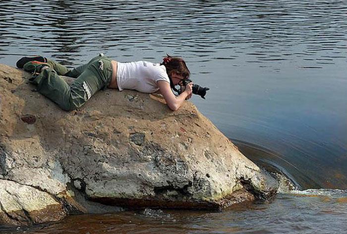 Una mujer tomando una foto acostada en una roca