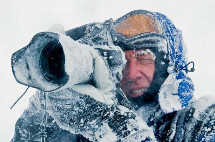 hombre tomando una fotografía con hielo alrededor de él y de su cámara