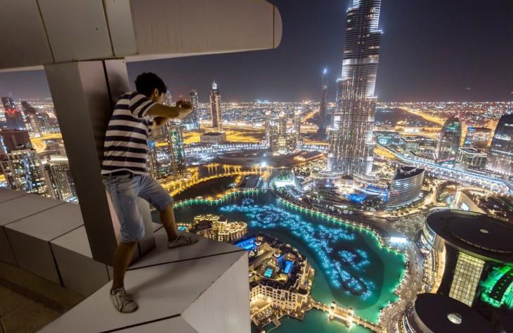 chico arriba de un edificio tomando una fotografía de una torre