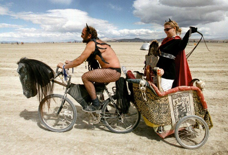 Un hombre en bicicleta estirando a una mujer sobre un carro con un látigo en el festival Burning Man