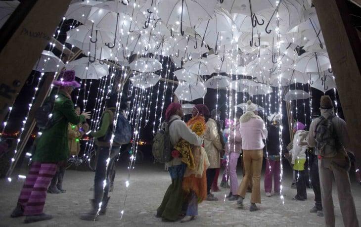 Personas debajo de muchas sombrillas blancas con luces en el festival Burning Man