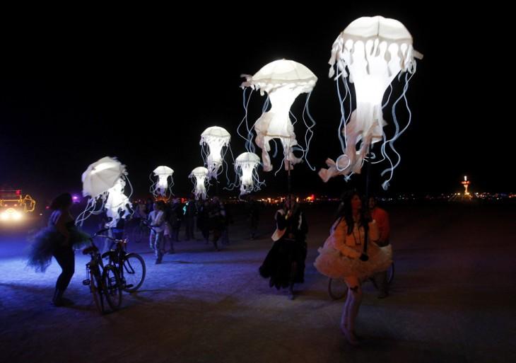 Festival Burning Man de noche muchas personas sosteniendo sombrillas en formas de medusas
