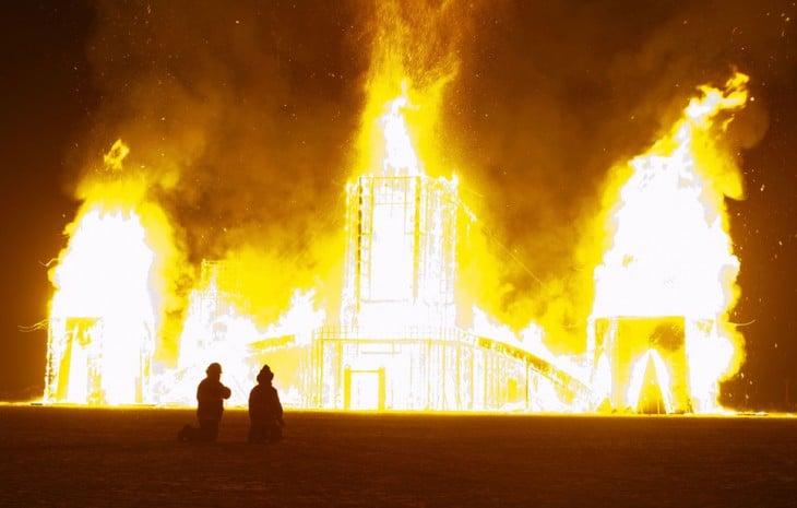 Personas viendo como se quema algo durante el Festival Burning Man