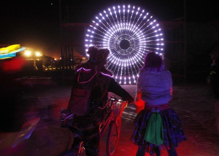 dos chicos en bicicleta observando unas luces en forma de círculo