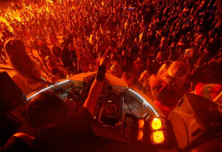 Dj y personas bailando y disfrutando de la noche durante los días del festival Burning Man en Nevada