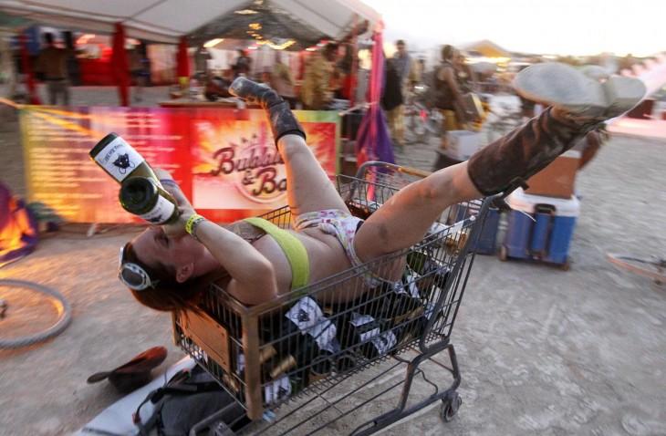 Mujer sobre un carrito de super tomando vino en el festival Burning Man