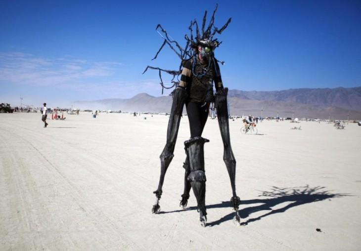 Hombre con brazos y manos grandes hechas con un material negro en el festival Burning -man
