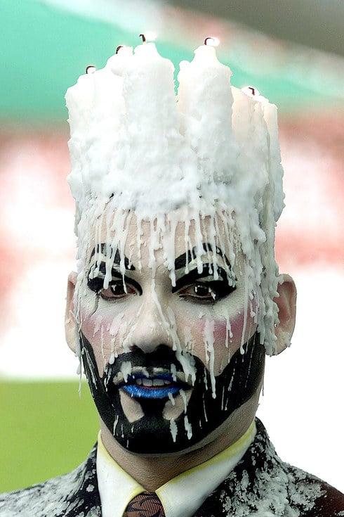 Un hombre con velas en su cabeza y con cera derretida en su cara en el festival Burning Man