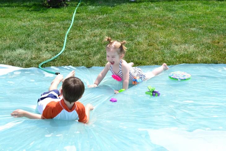 una niña y un niño acostados sobre un colchón de agua en el jardín