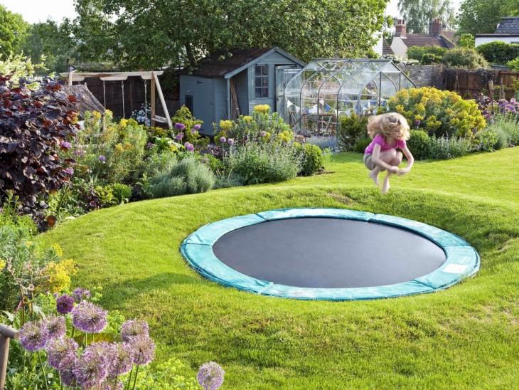 Niña saltando en un trampolín en el jardín