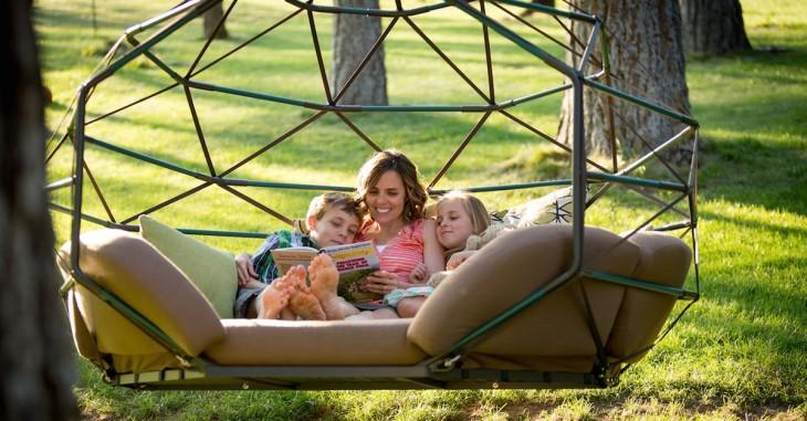 Mujer con dos niños a su lado en un sofá colgante