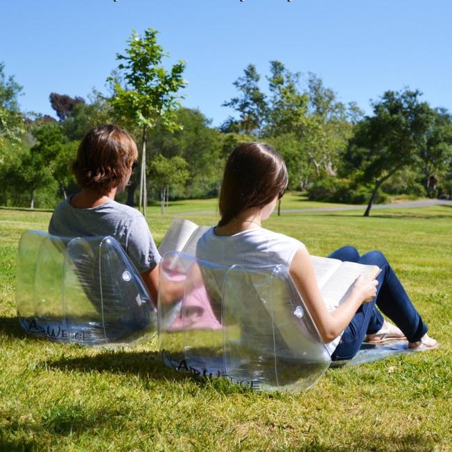 dos chicos al aire libre recargados en dos cojines inflables transparentes