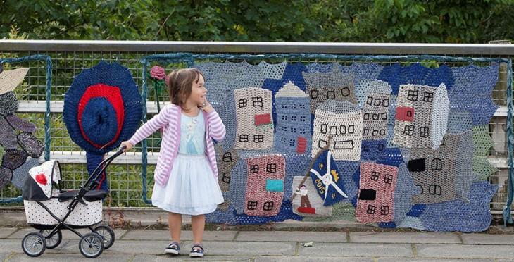 Niña sosteniendo una pequeña carreola por una calle de escocia