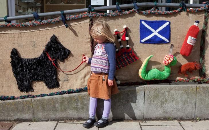 Niña sosteniendo en su mano la correa de un perro que esta tejido en una valla de una calle en Escocia