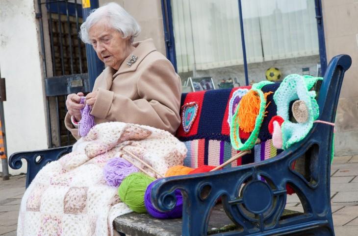 Mujer sentada en la banca de un parque en Escocia tejiendo