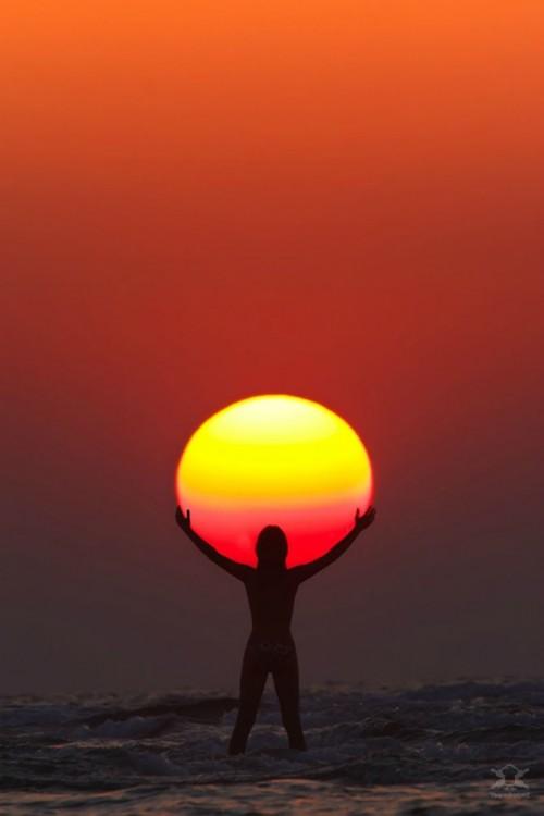 fotografía a contra luz de una persona sosteniendo el sol en un atardecer