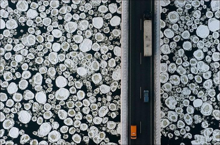 fotografía de carros pasando por un puente sobre agua con hielo