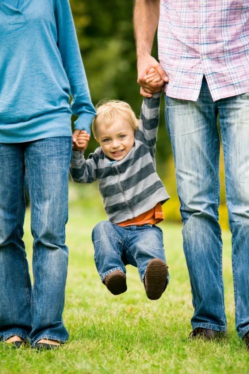 Dos personas balanceando a un niño directamente de las manos