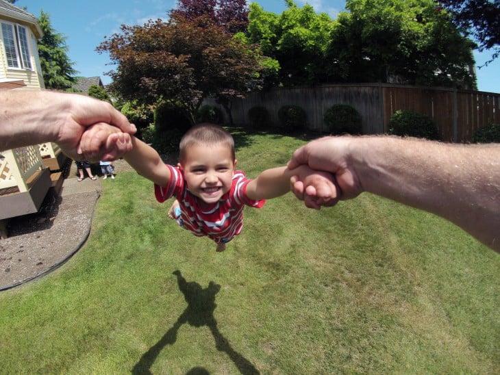 Persona sosteniendo a un niño de las manos y girando a un niño