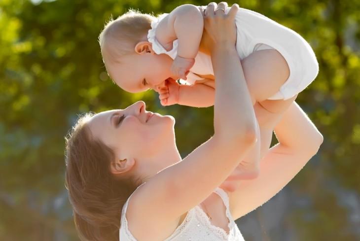 Mujer cargando a un bebé por debajo de sus brazos