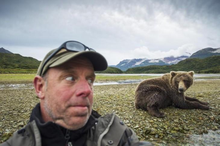 hombre tomando un selfie con un oso detrás de él