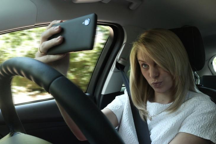 Chica tomándose una selfie mientras esta conduciendo