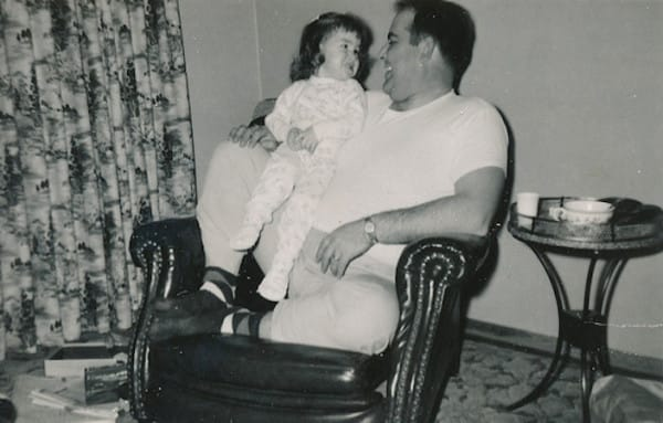 Fotografía de un hombre sentado en un sillón con una niña en sus brazos