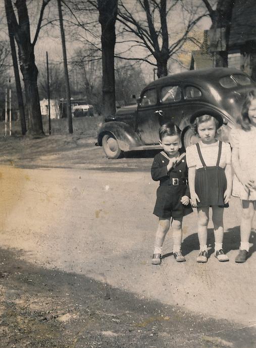 Fotografía de 3 niños parados en medio de una calle