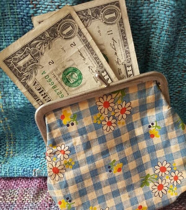 un pequeño monedero con dos dólares saliendo de él