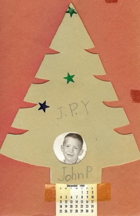 Pequeño pino de cartón con la fotografía de un niño en la parte inferior