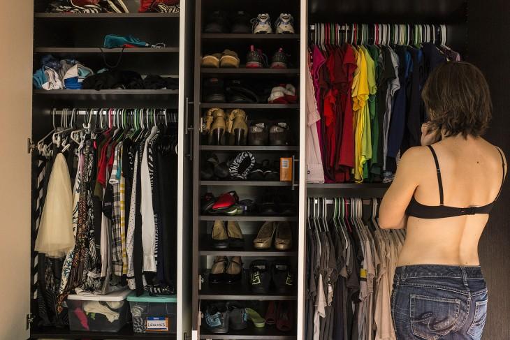 Una mujer parada frente a su closet pensando que se va a poner